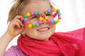 Portrait of cute little girl wearing funny glasses, decorated with colorful smarties, candies Royalty Free Stock Photo