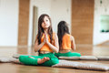 Portrait of a cute little smiling girl practicing yoga, in an orange suit, near a mirror