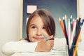 Portrait of cute lovely girl drawing in copybook on blackboard b Royalty Free Stock Photo