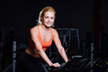Portrait of a cute nice female workout on  fitness  the exercise bike   dark at gym. Royalty Free Stock Photo