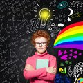 Portrait of cute redhead kid with light bulb. Curious child with colorful science and arts scetch. Kids education concept