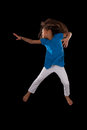 Portrait cute young african american girl jumping over black background Stock Photo
