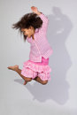 Portrait cute young african american girl jumping over gray background Stock Photography