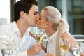 Portrait cute young couple kissing dinner table Royalty Free Stock Photography