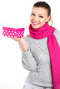 Portrait of cute young woman holding gift box in her hand a a gray sweater and a pink scarf a Stock Photo