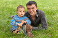Portrait of dad and son against the green grass Royalty Free Stock Photos
