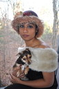Portrait of a dark lady beautiful young woman in elegant clothes is holding dog Stock Photography