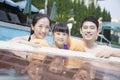 Portrait de famille de sourire dans la piscine par le bord regardant l appareil photo Photo stock