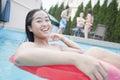 Portrait de jeune femme souriant et se reposant sur un tube gonflable dans la piscine Photos stock