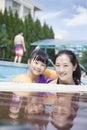 Portrait de mère et de fille de sourire dans la piscine par le bord regardant l appareil photo Photographie stock