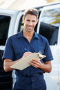 Portrait of delivery driver with clipboard smiling towards camera Stock Photos