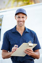 Portrait of delivery driver with clipboard smiling towards camera Royalty Free Stock Photo