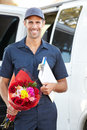 Portrait of delivery driver with flowers smiling to camera Stock Image