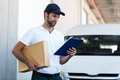 Portrait of delivery man is holding a cardboard box and looking a clipboard Royalty Free Stock Photo