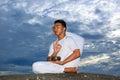 Portrait des asiatischen jungen Mannes, der Yoga auf Stein tut Stockfotografie