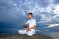 Portrait des asiatischen jungen Mannes, der Yoga auf Stein tut Lizenzfreie Stockbilder