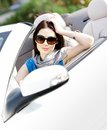 Portrait of dreamy woman in the cabriolet wearing sunglasses car and propping her head Stock Image
