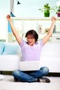 Portrait of ecstatic guy sitting with laptop and raised hands Stock Images
