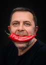 Portrait elderly man red pepper his mouth Royalty Free Stock Photo