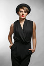 Portrait of elegant bussinesswoman wearing black clothes and a fashionable hat. Royalty Free Stock Photo