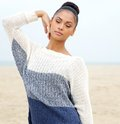 Portrait of an elegant young woman posing at the beach closeup in blue sweater Royalty Free Stock Photography