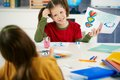 Portrait elementary age schoolgirl showing colorful paining to classmate art class primary school classroom Stock Image