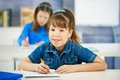 Portrait elementary age schoolgirl sitting class looking camera smiling other girl background Stock Images