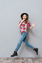Portrait of an excited young woman in plaid shirt jumping