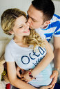 Portrait of expecting couple laughing happily embracing baby in belly together dressed blue and white colors Royalty Free Stock Photo