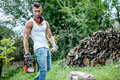 Portrait of expressive muscular lumberjack man with chainsaw and tank top in forest Royalty Free Stock Images