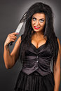 Portrait of an expressive young woman with creative make up hold holding a big knife on gray background Royalty Free Stock Photo