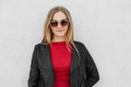Portrait of fair-haired female wearing sunglasses, red sweater and black leather jacket posing against white concrete wall. Pretty Royalty Free Stock Photo