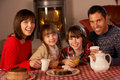 Portrait Of Family Enjoying Tea And Cake Stock Photography