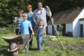 Portrait of family gardening outside cottage full length parents with three children Royalty Free Stock Photos