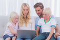 Portrait of a family using a laptop on the couch Royalty Free Stock Photography