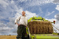 Portrait of farmer standing near machinery with straw bale Royalty Free Stock Photo
