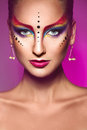 Portrait of fashion model with multicolor make up on purple back background in studio Royalty Free Stock Photo