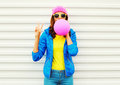 Portrait fashion pretty cool girl blowing pink air balloon in colorful clothes having fun over white background wearing a pink hat Royalty Free Stock Photo