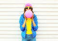Portrait fashion pretty cool girl blowing pink air balloon in colorful clothes having fun over white background wearing pink hat Royalty Free Stock Photo
