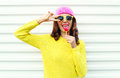 Portrait of fashion pretty cool girl with lollipop in colorful clothes over white background wearing a pink hat yellow sunglasses Royalty Free Stock Photo
