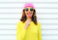 Portrait fashion pretty cool girl with lollipop in colorful clothes over white background wearing a pink hat yellow sunglasses Royalty Free Stock Photo