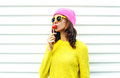 Portrait fashion pretty cool girl sucking lollipop in colorful clothes over white background wearing pink hat yellow sunglasses Royalty Free Stock Photo