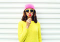 Portrait fashion pretty cool girl sucking lollipop in colorful clothes over white background wearing a pink hat yellow sunglasses Royalty Free Stock Photo