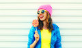 Portrait fashion pretty cool laughing woman with lollipop in colorful clothes over white background wearing a pink hat Royalty Free Stock Photo