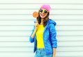 Portrait fashion pretty cool smiling woman with lollipop in colorful clothes over white background, wearing a pink hat Royalty Free Stock Photo