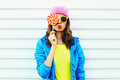 Portrait fashion pretty cool woman with lollipop in colorful clothes over white background wearing a pink hat yellow sunglasses Royalty Free Stock Photo