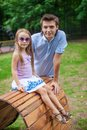 Portrait of father with his daughter sitting on the wooden plank bed in the park Stock Photos