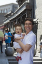 Portrait of father holding his baby son outdoors beijing Stock Image