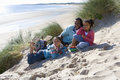 Portrait of father sitting with daughters on beach Royalty Free Stock Photo