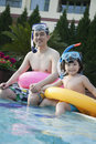 Portrait of father and son in snorkeling gear sitting by the edge of the pool Stock Photos